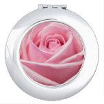 Color de rosa rosado en el espejo compacto redondo