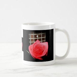 Color de rosa rosado rojo contra tablero del trast taza de café
