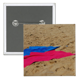 Colored towels on sandy beach 2 inch square button