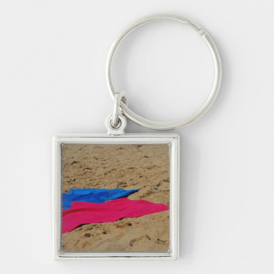 Colored towels on sandy beach keychain