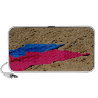 Colored towels on sandy beach mini speakers