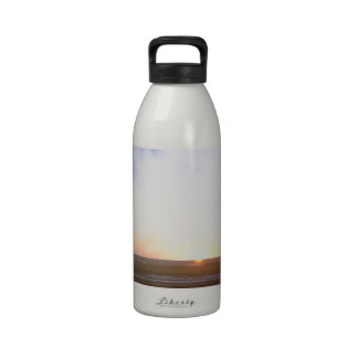 Colorful beach at sunset with flying birds reusable water bottle