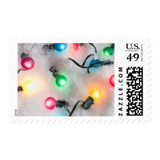 Colorful Christmas lights glowing in the snow Postage
