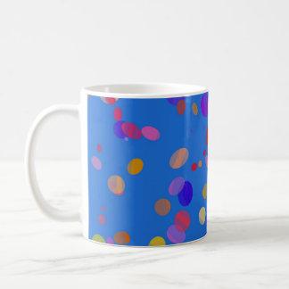 Colorful confetti over blue coffee mug
