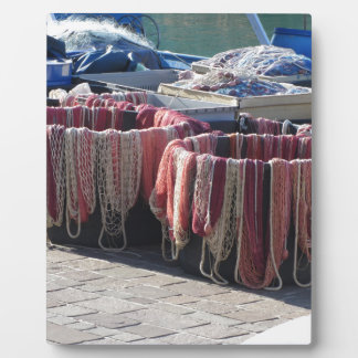 Colorful fishing nets in the harbor . Tuscany Plaque