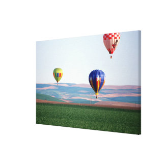 Colorful hot air balloons float over wheat canvas print