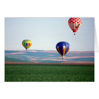 Colorful hot air balloons float over wheat greeting card