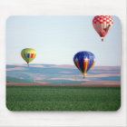 Colorful hot air balloons float over wheat mouse pad