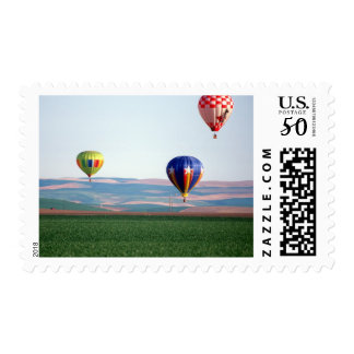 Colorful hot air balloons float over wheat postage