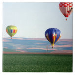Colorful hot air balloons float over wheat large square tile