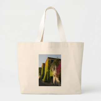 Colorful leaves on house walls large tote bag