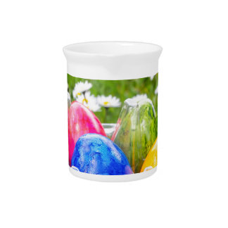 Colorful painted easter eggs in grass with daisies pitchers