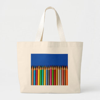 Colorful pencil crayons on blue background large tote bag