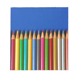 Colorful pencil crayons on blue background notepad