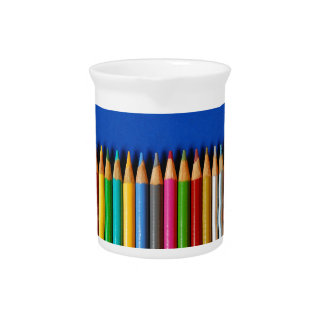 Colorful pencil crayons on blue background pitcher