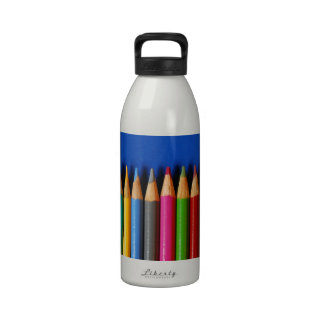 Colorful pencil crayons on blue background water bottles