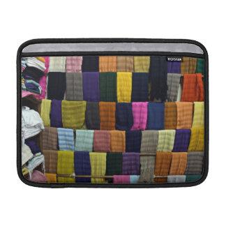 Colorful scarves on display sleeves for MacBook air