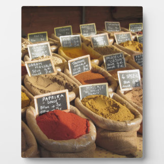Colorful spices in jute bags at the local market plaque