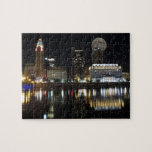 """Columbus Skyline with the Moon Jigsaw Puzzle<br><div class=""""desc"""">A classic view of the Columbus,  Ohio skyline and cityscape from Genoa Park on the opposite side of the Scioto River at night with reflections sitting on the water and the moon overhead.</div>"""