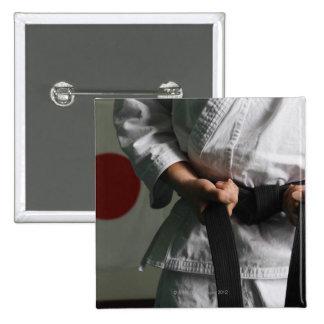 Combatiente del Taekwondo que tensa la correa Pin Cuadrado