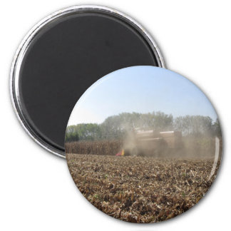Combine harvesting corn crop in cultivated field magnet