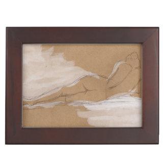 Composición desnuda femenina que miente en cama caja de recuerdos