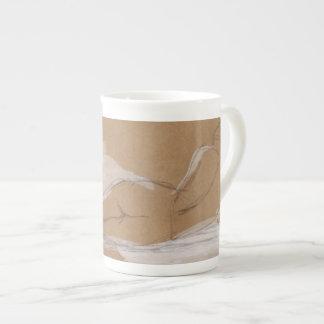Composición desnuda femenina que miente en cama taza de porcelana