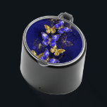 """Composition with Sapphire Butterflies Bluetooth Speaker<br><div class=""""desc"""">Composition of luxurious sapphire and gold jewelry butterflies on blue textured background.</div>"""