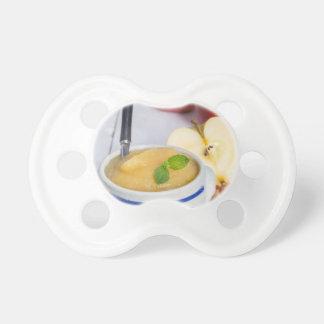 Compota de manzanas con canela en cuenco del gres chupetes para bebes