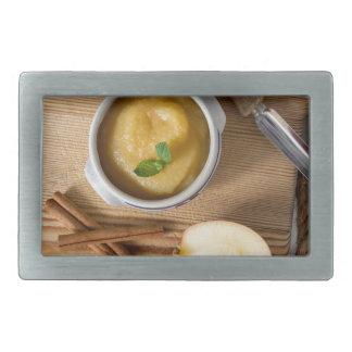 Compota de manzanas con canela en cuenco del gres hebilla cinturón rectangular