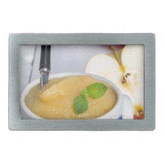 Compota de manzanas con canela en cuenco del gres hebillas cinturon rectangulares