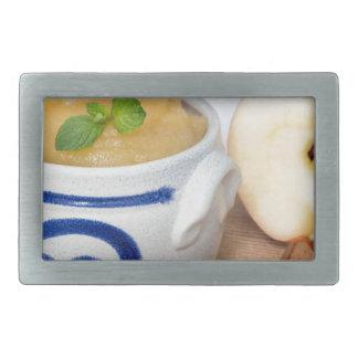 Compota de manzanas con canela en cuenco del gres hebillas cinturón rectangulares