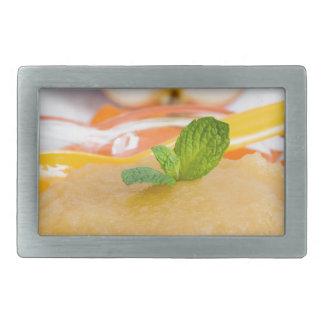 Compota de manzanas con la cuchara del canela y hebillas cinturon rectangulares