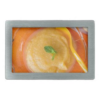 Compota de manzanas con la cuchara del canela y hebillas de cinturón rectangulares