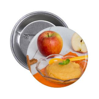Compota de manzanas con la cuchara del canela y pin redondo de 2 pulgadas