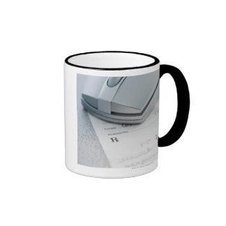Computer mouse on written prescription coffee mug