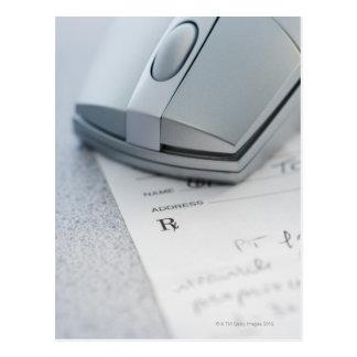 Computer mouse on written prescription postcard