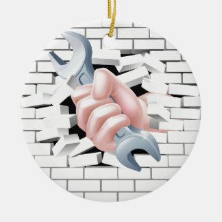 Concepto de la llave inglesa de la mano adorno navideño redondo de cerámica