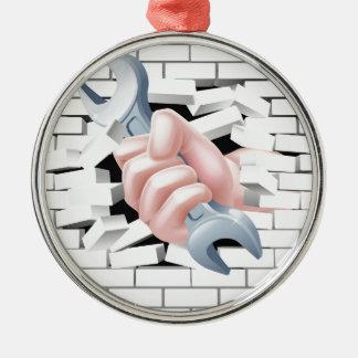 Concepto de la llave inglesa de la mano adorno navideño redondo de metal