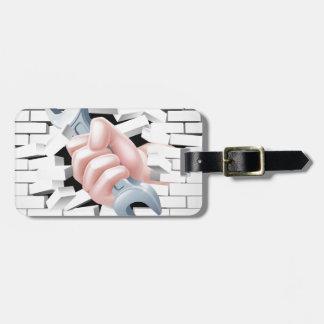 Concepto de la llave inglesa de la mano etiquetas para maletas