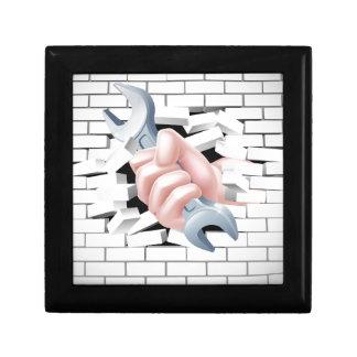 Concepto de la llave inglesa de la mano joyero cuadrado pequeño
