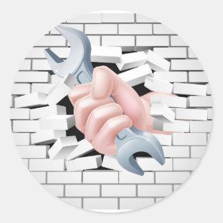 Concepto de la llave inglesa de la mano pegatina redonda