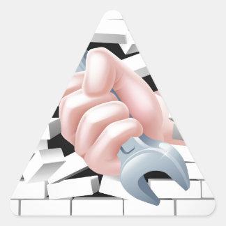 Concepto de la llave inglesa de la mano pegatina triangular