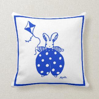 Conejito azul y amarillo con la almohada de la com