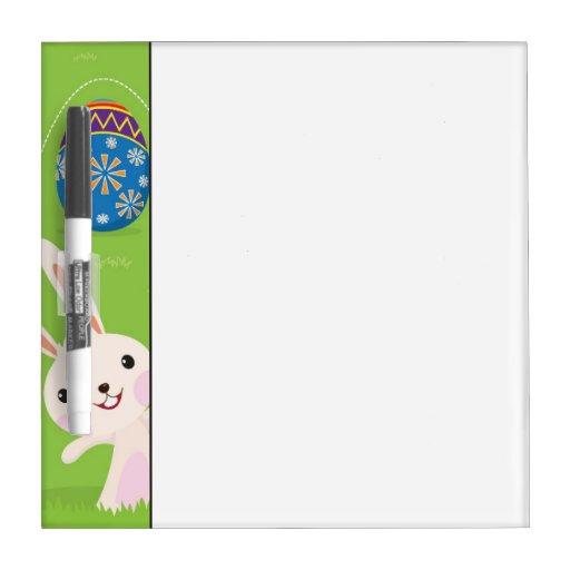 Conejito de pascua juguetón con los huevos pintado pizarra blanca
