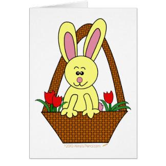 Conejito de pascua lindo del dibujo animado en una tarjeta de felicitación