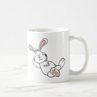 Conejito de pascua lindo que se enfría hacia fuera taza de café