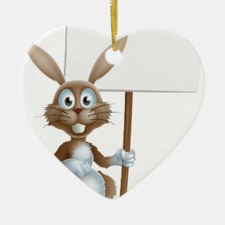 Conejito de pascua que lleva a cabo la muestra adorno navideño de cerámica en forma de corazón