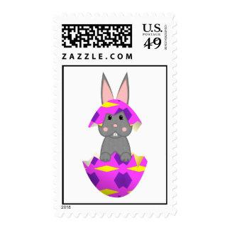 Conejito gris en un huevo rosado franqueo