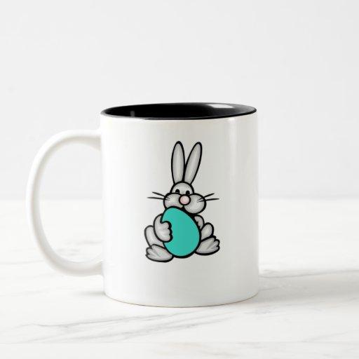 Conejito que sostiene el huevo verde de la turques tazas de café